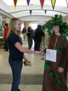 Team member Emily Simmons hands Dara Stillman (tree) flower packets on Earth Day